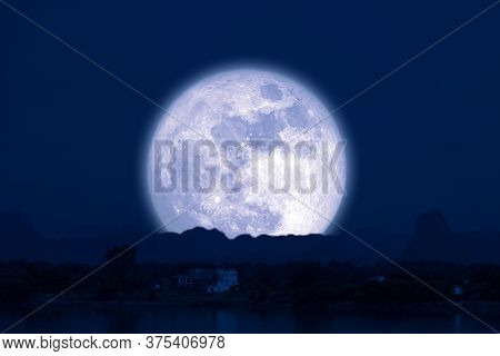 Full Snow Moon On Night Sky Back Silhouette Mountain Hill Over Lake