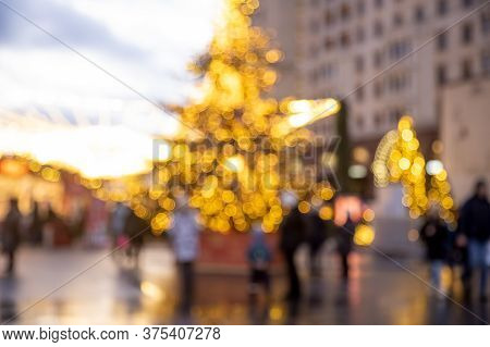 Christmas Holiday Background. Christmas Tree In Shining Garland At New Years Outdoor Daylight Market
