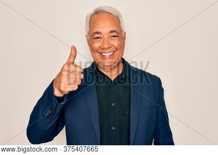 Middle age senior grey-haired handsome man wearing elegant business jacket doing happy thumbs up gesture with hand. Approving expression looking at the camera showing success.