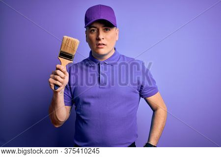 Young modern decorator painter man holding paint brush over purple background with a confident expression on smart face thinking serious