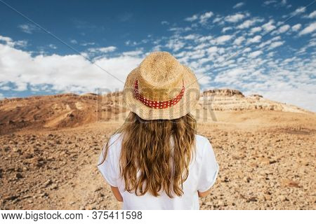 Girl In Straw Hat Watching Negev Desert In Israel. Mitzpe Ramon Crater Landscape. Lifestyle And Trav
