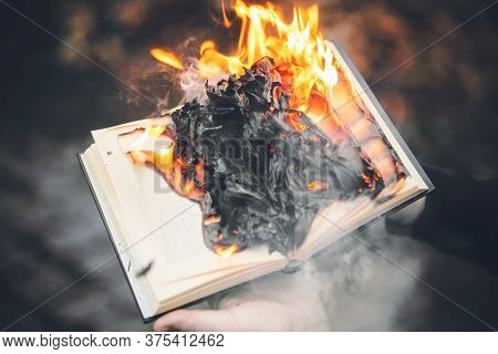 A Person Holds An Old Book In His Hands, The Pages Of Which With Wise Texts Blaze With A Bright Flam