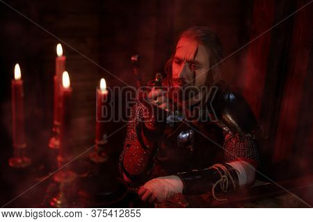 An experienced medieval warrior in armor and with a sword in a wooden house. Stage portrait. The Witcher man.
