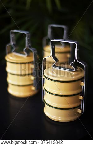 Yellow 3 Tiers Tiffin Carriers On Black Table Background
