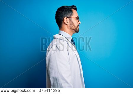 Young handsome doctor man with beard wearing coat and glasses over blue background looking to side, relax profile pose with natural face with confident smile.