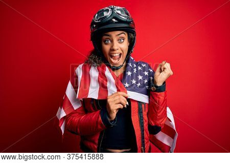 African american patriotic motorcyclist girl wearing moto helmet wearing united states flag screaming proud and celebrating victory and success very excited, cheering emotion