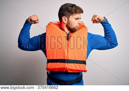 Young blond tourist man with beard and blue eyes wearing lifejacket over white background showing arms muscles smiling proud. Fitness concept.