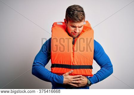 Young blond tourist man with beard and blue eyes wearing lifejacket over white background with hand on stomach because indigestion, painful illness feeling unwell. Ache concept.