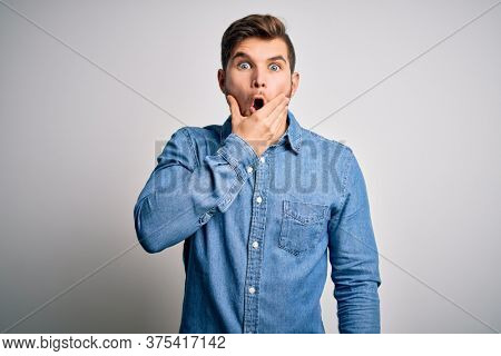 Young handsome blond man with beard and blue eyes wearing casual denim shirt Looking fascinated with disbelief, surprise and amazed expression with hands on chin