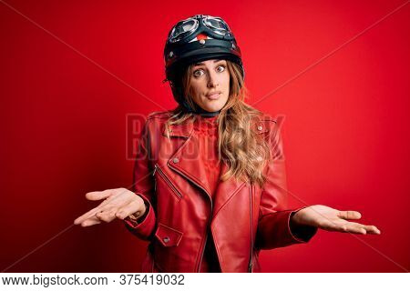 Young beautiful brunette motrocyclist woman wearing moto helmet over red background clueless and confused expression with arms and hands raised. Doubt concept.