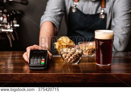 Modern Payment At Bar. Barman In Apron Gives To Client A Glass Of Dark Beer, Snacks And Terminal On