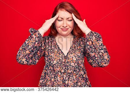 Young beautiful redhead woman wearing floral casual dress standing over red background with hand on head, headache because stress. Suffering migraine.