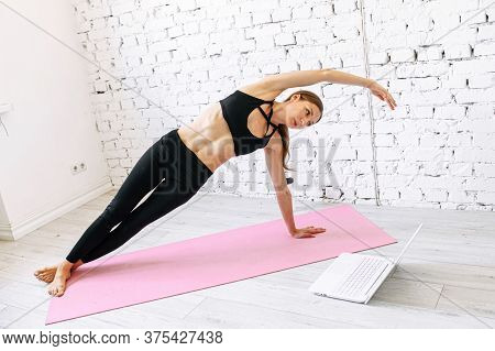 Online Yoga Practice Of A Young Woman. Good Looking Girl Is Repeating Online Yoga Moves And Poses Us