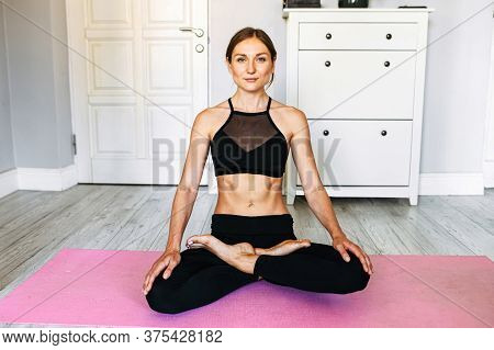 Peaceful Young Beautiful Girl Sits In Lotus Pose, She Looks Into The Camera With A Calm Kind Look On
