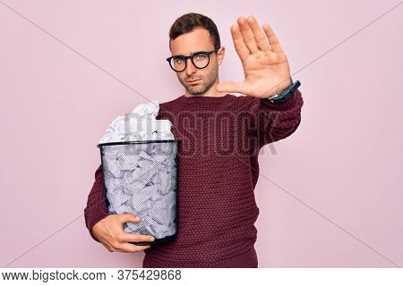Handsome man with blue eyes wearing glasses holding full paper bin with crumpled papers with open hand doing stop sign with serious and confident expression, defense gesture