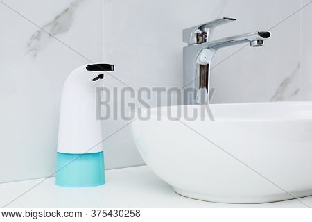 Modern Automatic Soap Dispenser Near Sink In Bathroom, Closeup