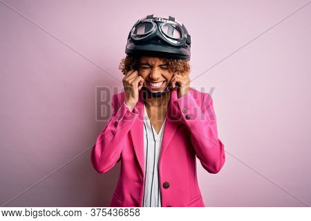 African american motorcyclist woman with curly hair wearing moto helmet over pink background covering ears with fingers with annoyed expression for the noise of loud music. Deaf concept.