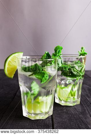 Mojito Cocktail Or Soda Drink With Lime And Mint Isolated On Wood Background. High Quality Photo