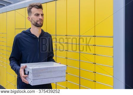 Man Holding Parcel And Sending Using Yellow Self-service Post Terminal Machine. Client Received Parc