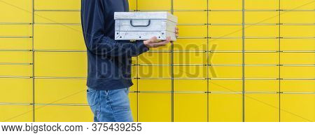 Parcel Holding In Hands And Sending Using Yellow Self-service Post Terminal Machine. Hands With Ship
