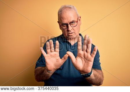 Middle age handsome hoary man wearing casual polo and glasses over yellow background Moving away hands palms showing refusal and denial with afraid and disgusting expression. Stop and forbidden.
