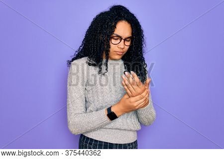 Young african american woman wearing casual sweater and glasses over purple background Suffering pain on hands and fingers, arthritis inflammation