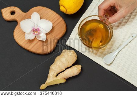 Health Remedy Foods For Cold And Flu Relief. Female Hand With A Cup Of Tea And Lemon, Ginger On A Bl