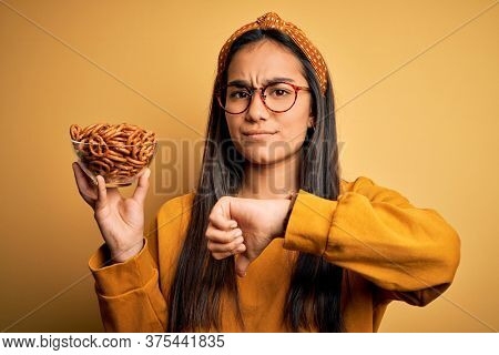 Young beautiful asian woman holding bowl with german baked pretzels over yellow background with angry face, negative sign showing dislike with thumbs down, rejection concept