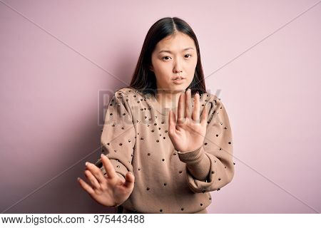 Young beautiful asian woman wearing fashion and elegant sweater over pink solated background Moving away hands palms showing refusal and denial with afraid and disgusting expression. Stop, forbidden.