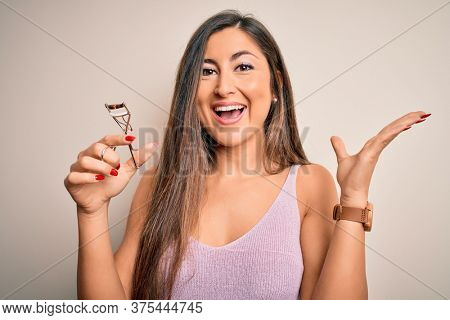 Young beautiful brunette woman holding eyelash curler over isolated white background very happy and excited, winner expression celebrating victory screaming with big smile and raised hands