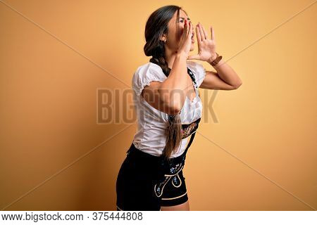 Young beautiful brunette german woman celebrating Octoberfest wearing traditional dress Shouting angry out loud with hands over mouth