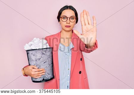 Young beautiful business woman with blue eyes holding heap bin of crumpled papers with open hand doing stop sign with serious and confident expression, defense gesture