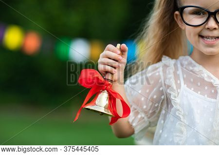 Portrait Of Little Blond Girl With Tails And Glasses Ringing Gold School Bell Against Flags Backgrou