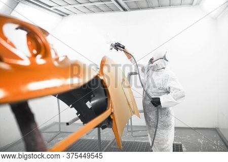 Man In Protective Mask And Clothes Sprays Varnish To Car Hood With A Spray Gun In A Paint Booth.