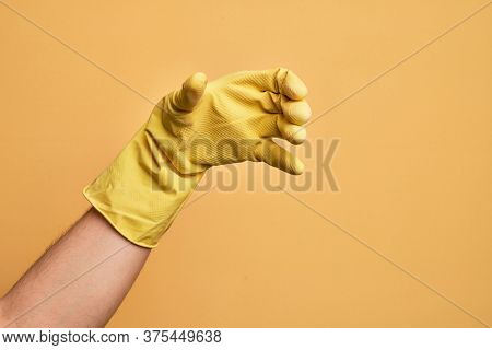Hand of caucasian young man with cleaning glove over isolated yellow background holding invisible object, empty hand doing clipping and grabbing gesture