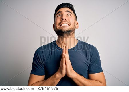 Young handsome man wearing casual t-shirt standing over isolated white background begging and praying with hands together with hope expression on face very emotional and worried. Begging.