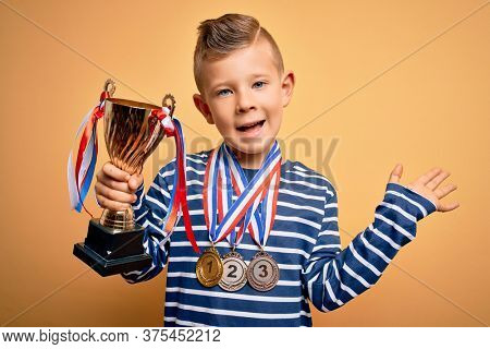Young little caucasian kid wearing winner medals and victory award trophy over yellow background very happy and excited, winner expression celebrating victory screaming with big smile and raised hands