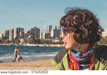 Profile Of A Brunette Woman With Curly Hair, Colorful Clothings And Sunglasses, Sitting On Sandy Bea