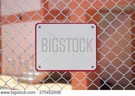 The White Metal Sign Is Installed On The Metal Mesh Fence.