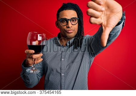 Young african american afro sommelier man with dreadlocks drinking glass of wine with angry face, negative sign showing dislike with thumbs down, rejection concept