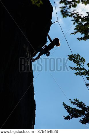 Silhouette Of Female Alpinist Climbing Extremely Vertical Rock Under Blue Sky. Young Woman Ascending