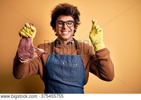 Young handsome butcher man holding meet steak standing over isolated yellow background gesturing finger crossed smiling with hope and eyes closed. Luck and superstitious concept.