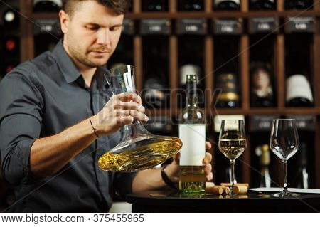 Sommelier Decants White Wine In Decanter Over Cellar Of Bottle Background