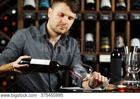 Sommelier Pouring Red Wine From Bottle In Glass