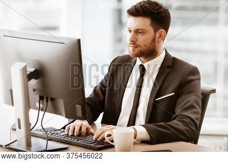 Business concept. Successful young businessman at work. Manager sitting at the office table and working on computer. Busy man in suit indoors on glass window background.