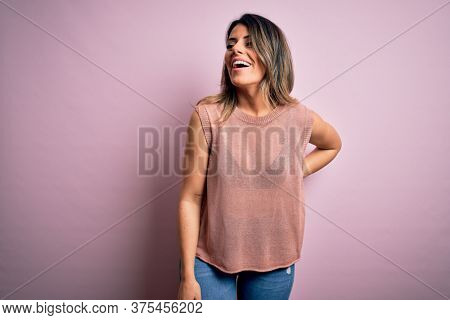 Young beautiful woman wearing fashion urban clothes, model wearing casual street style standing over pink background