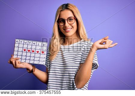 Young beautiful blonde woman holding period calendar to control menstrual cycle very happy pointing with hand and finger to the side