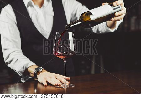 Close Up Shot Of Sommelier Pouring Red Wine From Bottle In Glass