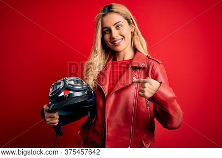 Young beautiful blonde motorcyclist woman holding moto helmet over isolated red background with surprise face pointing finger to himself