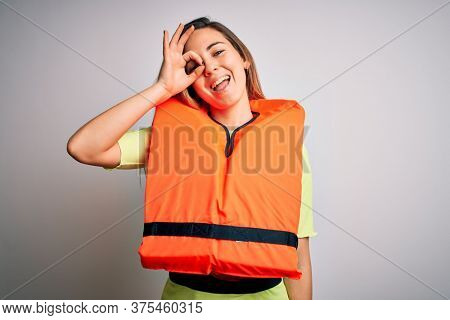 Young beautiful blonde woman with blue eyes wearing orange lifejacket over white background doing ok gesture with hand smiling, eye looking through fingers with happy face.